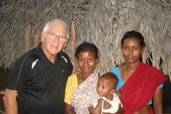 Alan with family in hut INdia
